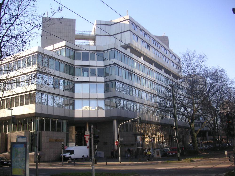 Deutsch-Japanisches Center Düsseldorf, ein hellgraues, mehrstöckiges Bürogebäude an einer Straßenecke mit großen Fenstern über die breite Front.
