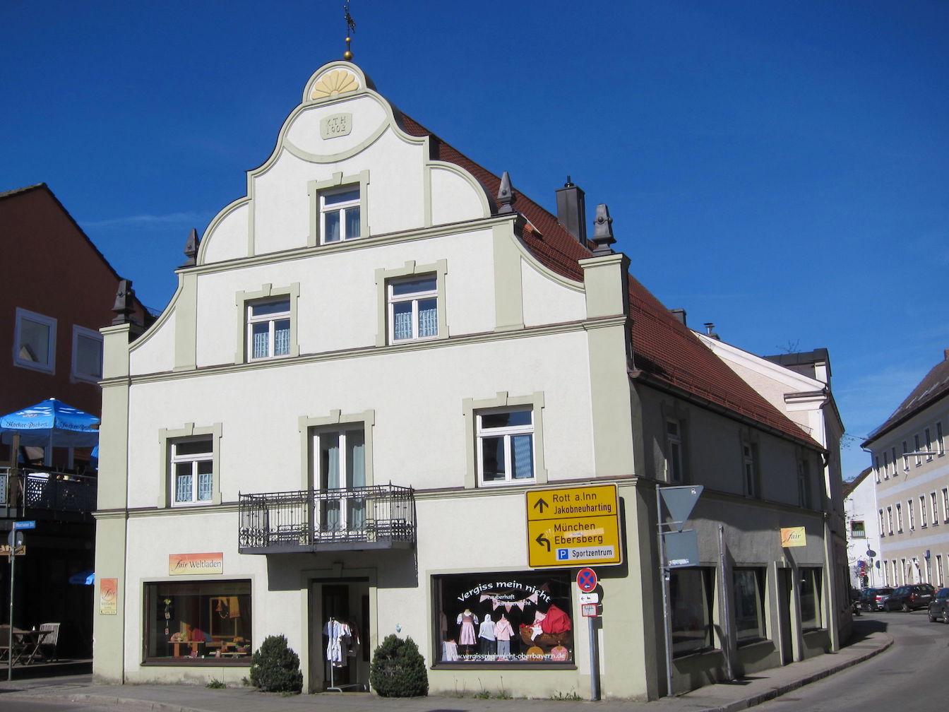 Vierstöckiges, weißes Gebäude mit geschwungenem Giebel am Marktplatz von Grafing, im Erdgeschoss Schaufenster für zwei Läden