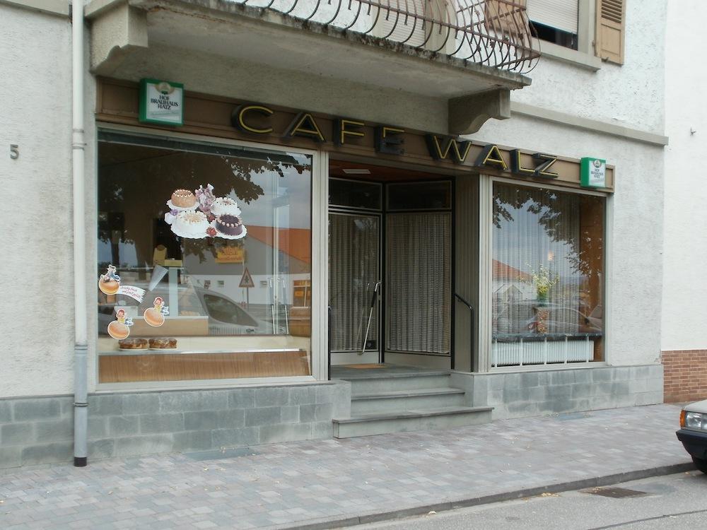 Café im Stil der 1980er Jahre: Schaufenster mit Gardinen und Theke, Eingang über Stufen und Tür mit gerippter Türklinke