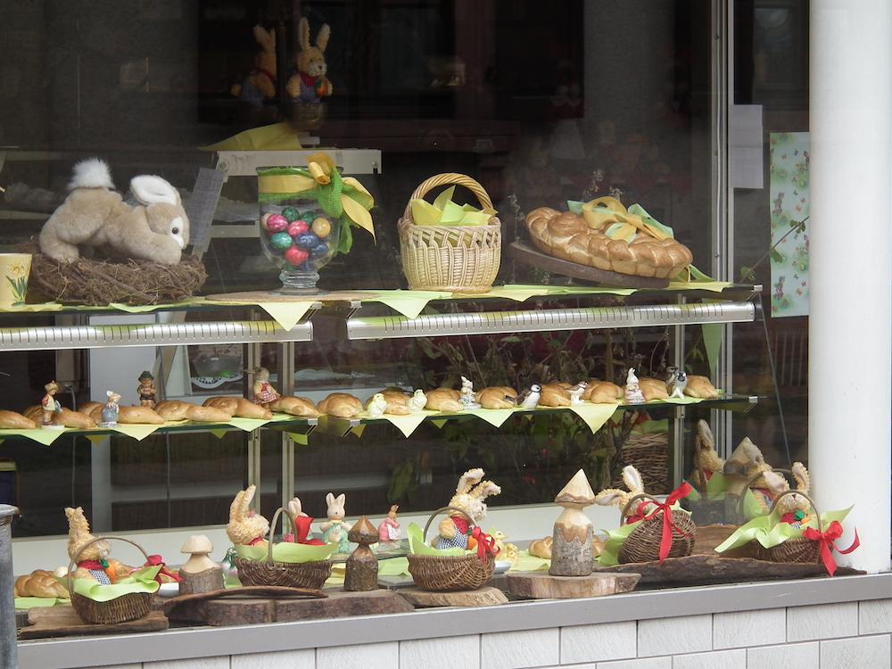 Blick in das Schaufenster einer Bäckerei. Auf drei Regalen stehen geflochtene Körbe, Stoffhasen, ein Glas mit gefärbten Eiern, zwischen Hefegebäck kleine Osterhasenfiguren aus Porzellan.