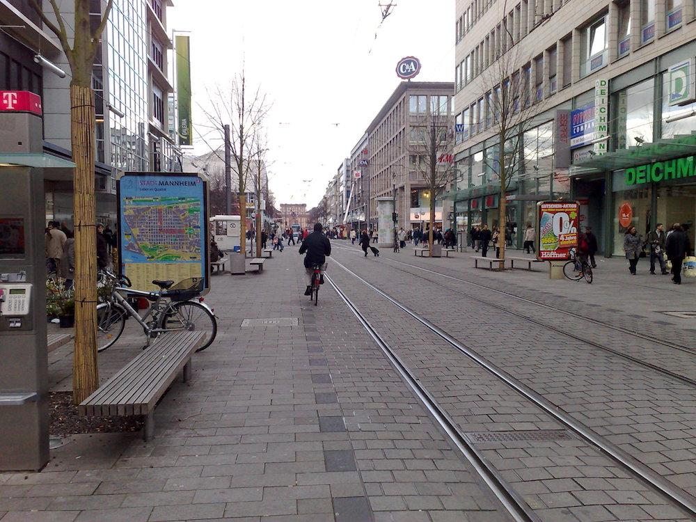 """Blick auf die Fußgängerzone """"Breite Straße"""" in Mannheim. Links eine Straßenbahnhaltestelle, rechts an der Fassade """"C&A"""", im Hintergrund das Mannheimer Schloss."""