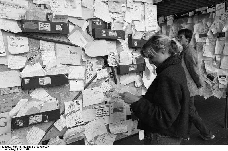 Schwarzweiß-Foto einer Studentin vor einem Schwarzen Brett, an dem handgeschriebene Zettel kleben, die für Mitfahr- und Mitwohngelegenheiten werben.