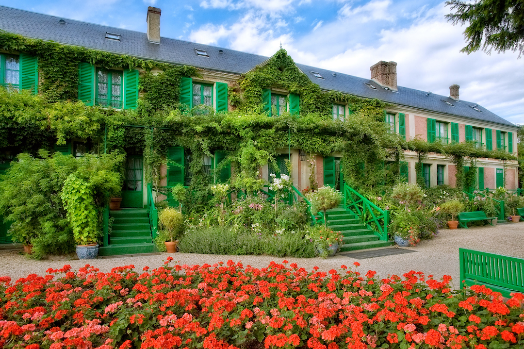 Zweistöckiges, langgezogenes Haus von Claude Monet mit bodentiefen Fenstern und grünen Fensterläden, grüne Treppen hinauf zu den Eingängen; die Fassade bewachsen mit Wein; vor dem Gebäude Blumenrabatten und Topfpflanzen. Im Vordergrund ein Beet voller rot leuchtender Geranien.