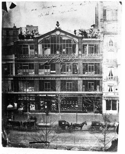 """Schwarzweiß-Fotografie des Fotostudios von Nadar in Paris, eines vierstöckigen Hauses mit großen Fensterfronten. Quer über das 3. Geschoss ist in fließender Schrift der Neon-Schriftzug """"Nadar"""" angebracht. Auf der Straße vor dem Haus stehen Pferdekutschen."""