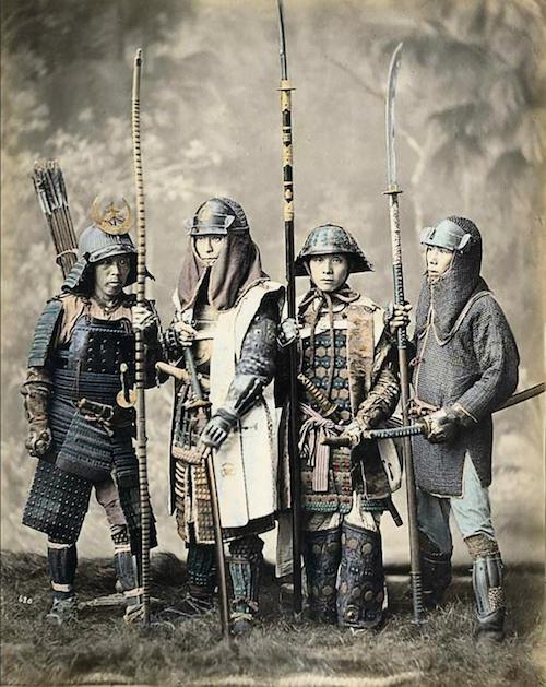 Das nachkolorierte Foto von Felice Beato zeigt 4 Samurai in voller Rüstung mit Helm und Waffen.