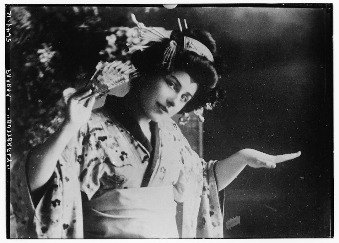 Schwarzweiß-Foto der Tänzerin Geraldine Farrar in japanischer Tracht: mit Kimono, schwarzer Perücke mit Haarschmuck und einem Fächer in der Hand