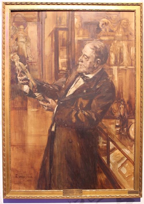 Das Portrait zeigt Émile Guimet vor Vitrinen und Ausstellungsregalen. Er betrachtet mit Sachverstand eine Statue.