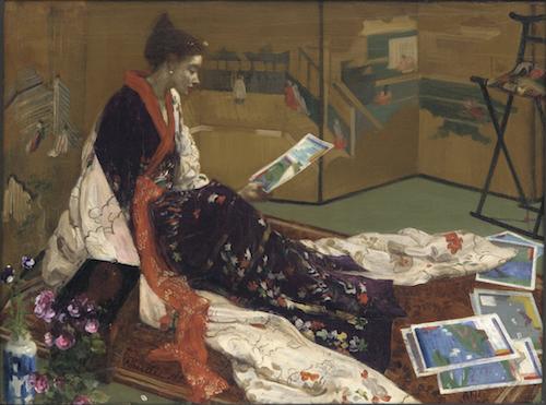 """James McNeill Whistlers """"Caprice in Purple and Gold"""" sitzt im Kimono am Boden und betrachtet japanische Holzschnitte. Hinter ihr steht ein japansicher Wandschirm, neben sich hat sie ein japanisches Schränkchen und eine Vase."""
