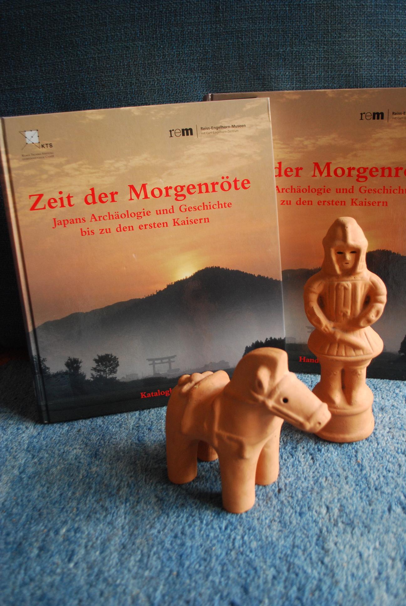 """Haniwa-Figuren vor Katalog und Handbuch """"Zeit der Morgenröte"""""""